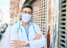 Doctor wearing uniform and coronavirus protection medical mask standing at town street.