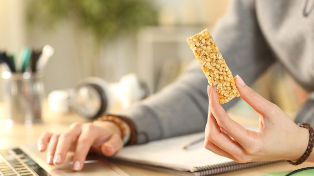 eating a protein bar at a desk with a laptop