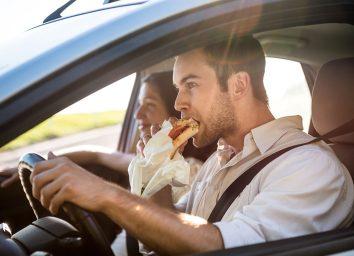 man eating in car