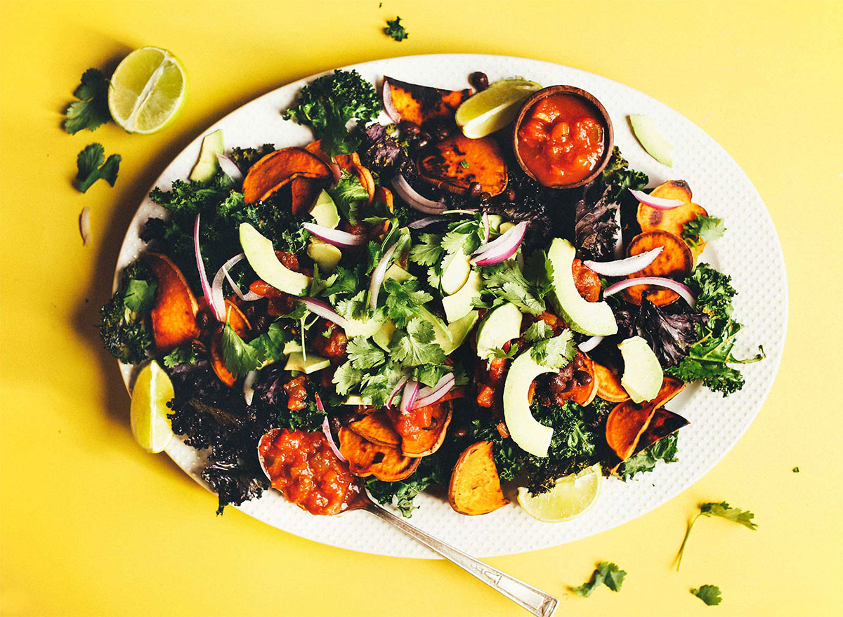 kale nachos topped with cilantro and avocado