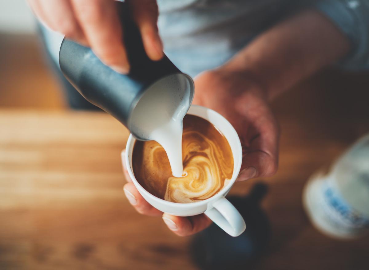 Man barista making coffee latte