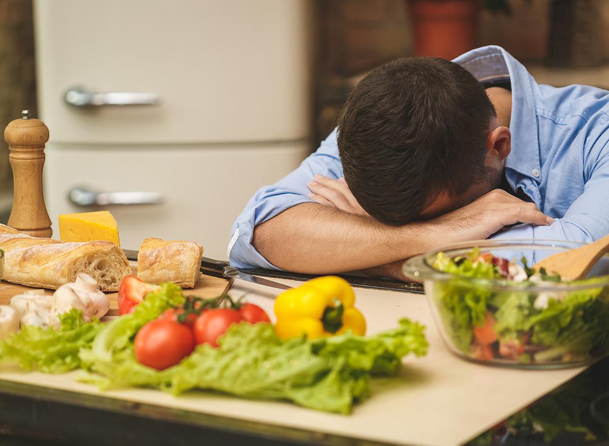 stressed man head down in kitchen