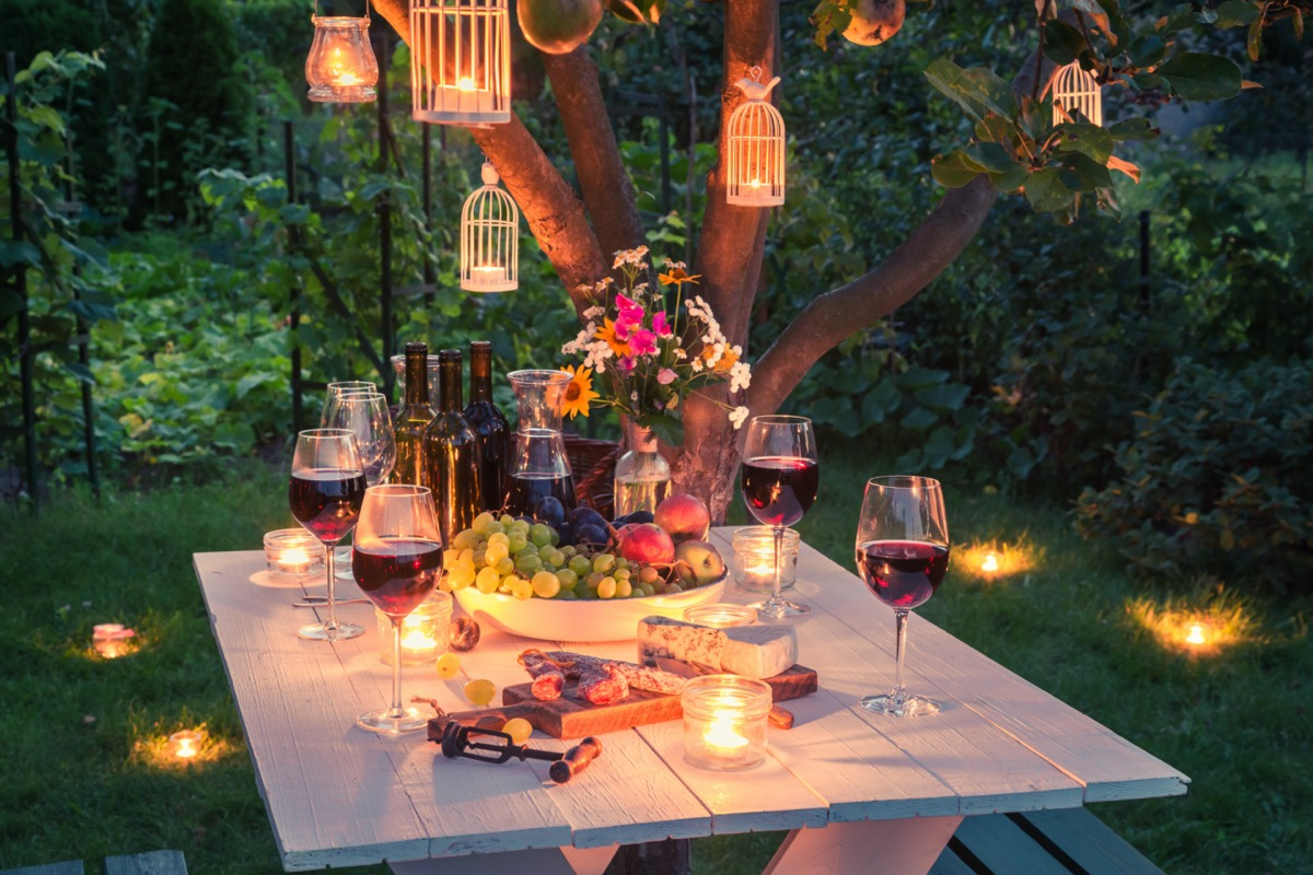 table full of cheese and meats in garden at dusk