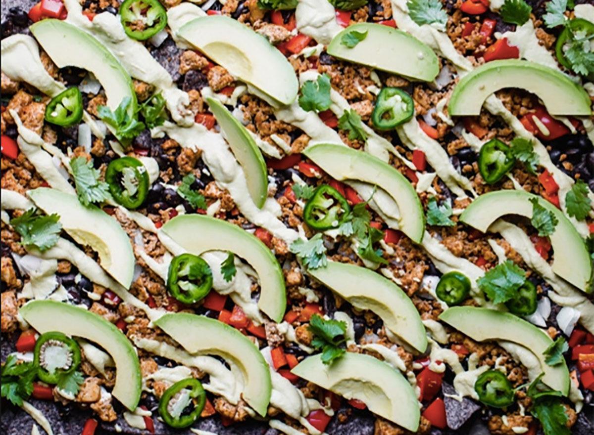 vegan nachos topped with avocado and jalapeno