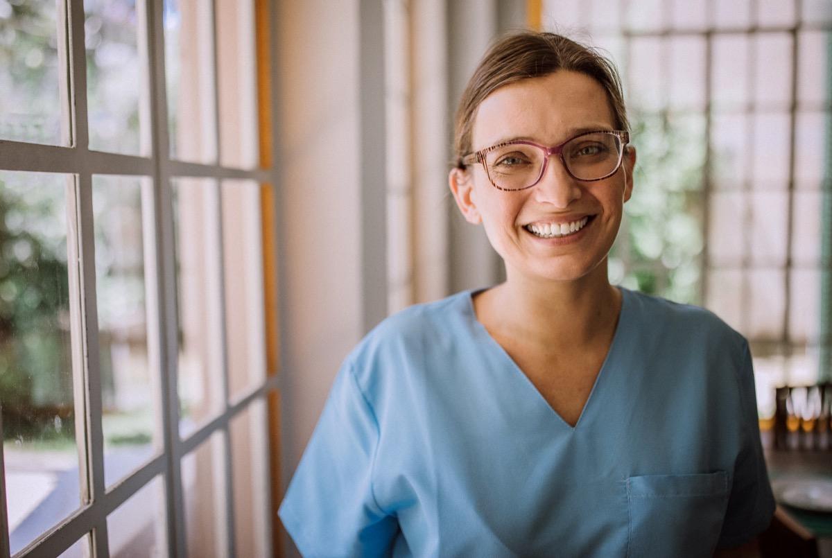 Smiling female nurse in medical scrubs.