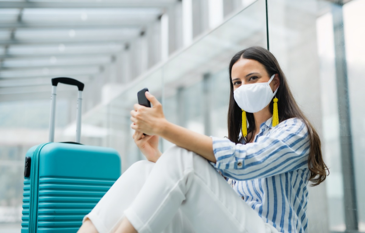 woman with smartphone going on holiday, wearing face masks at the airport
