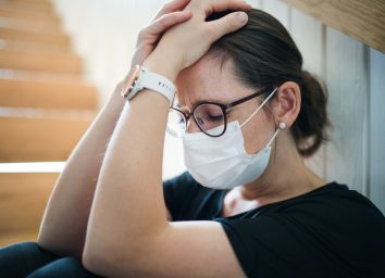 Sad woman with face mask sitting indoors at home,