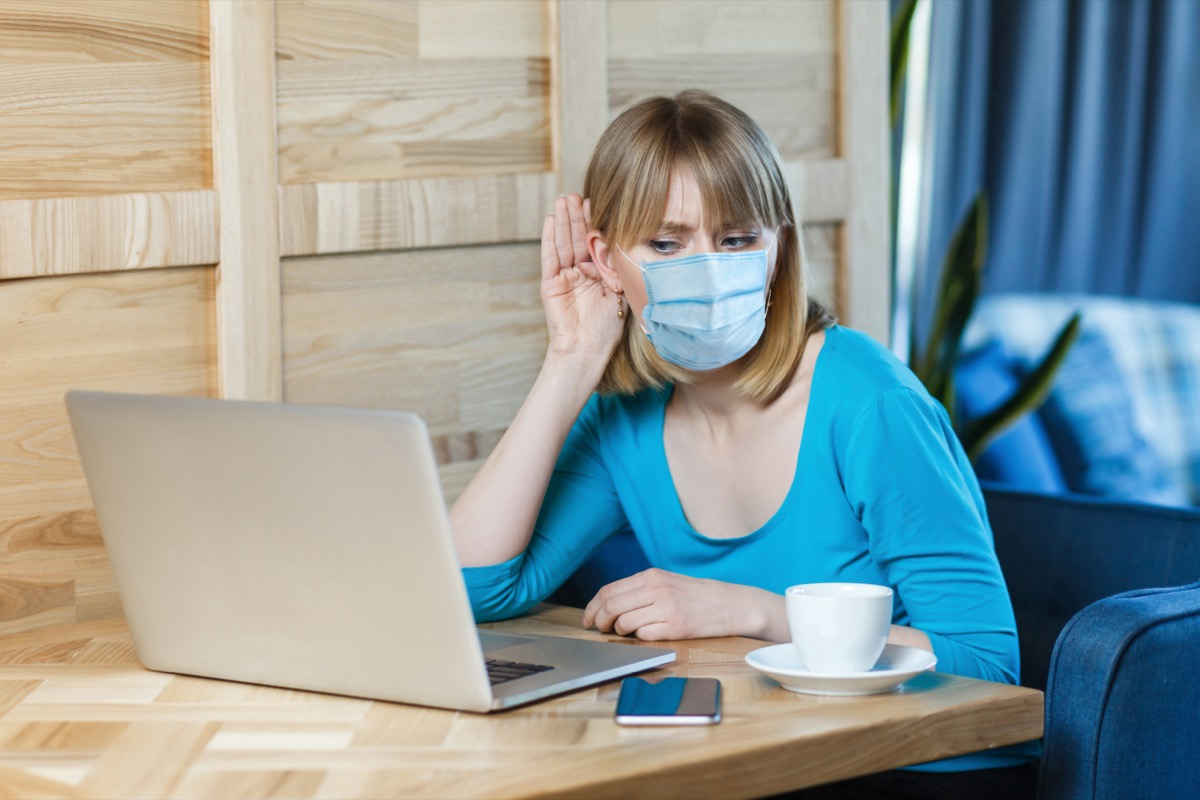 woman with surgical medical mask is sitting and working on laptop and trying to hear with attention to laptop