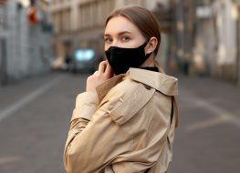Woman wearing coat during walk on an empty street.