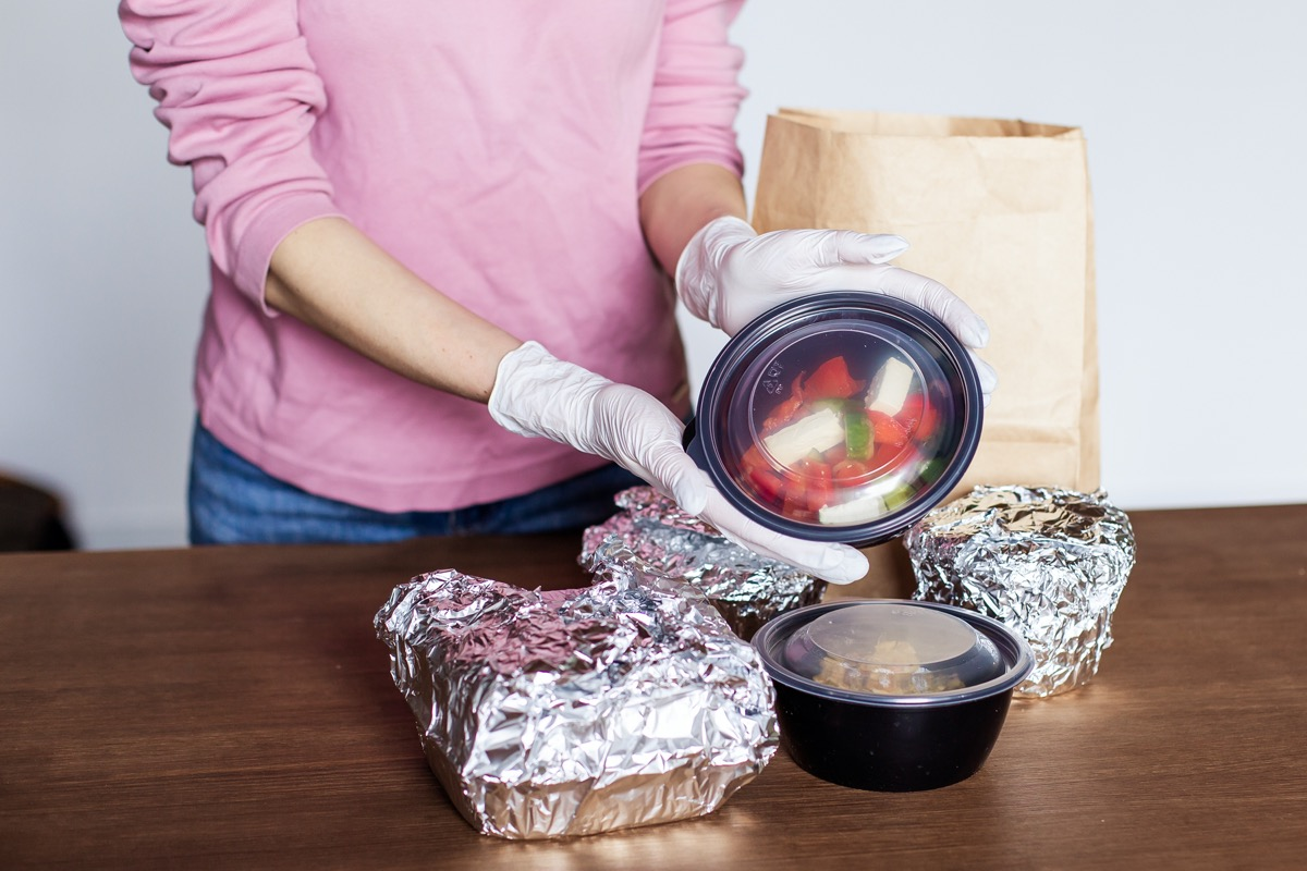 woman at kitchen home unpacks packing safely dinner