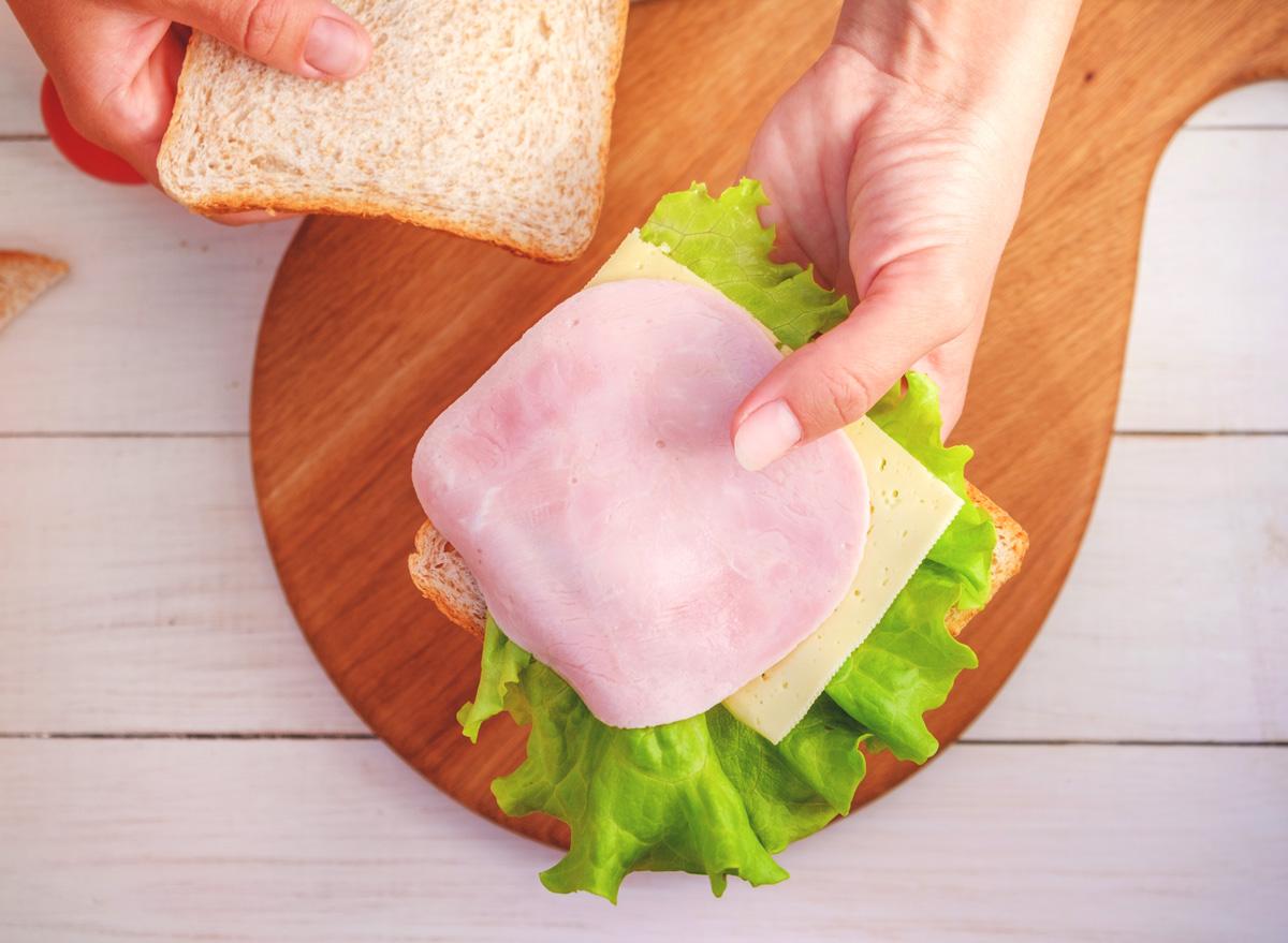 woman making sandwich bread lettuce cheese deli meat for lunch