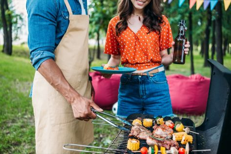 woman with beer looking at african american boyfriend cooking food on grill during barbecue