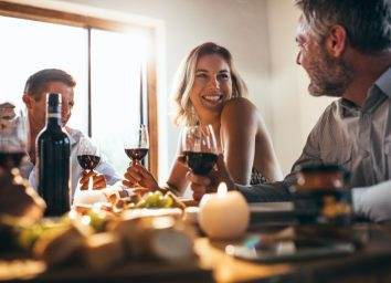 Smiling woman talking with friends sitting at dining tablet at home. Group of people having great time at dinner party.