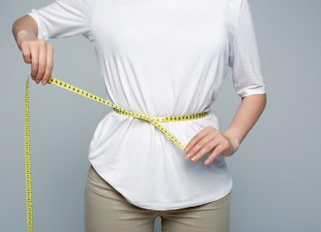 woman in white shirt measuring waist with tape