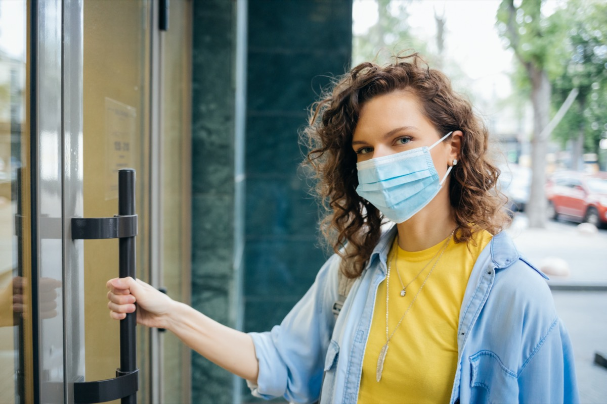 woman in protective mask opens the door