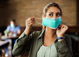 Woman putting on face mask while sitting in a cafe during coronavirus.