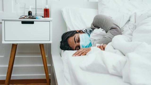 Woman sleeps in bed with a face mask on