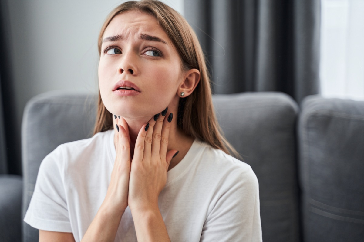 woman touching her neck and feeling pain in throat while sitting in the living room at home.