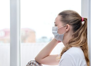 Woman sits at window in a medical mask.