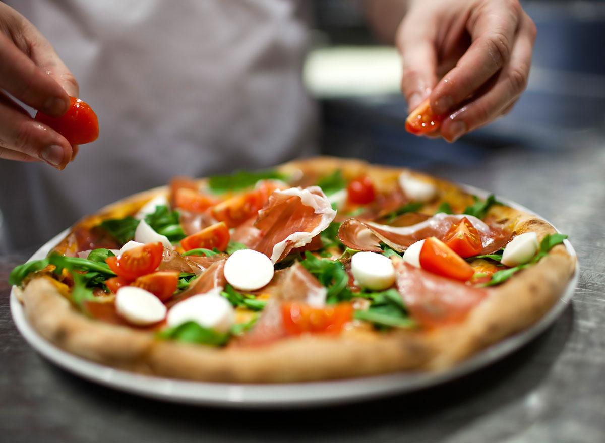 pizza adding tomatoes