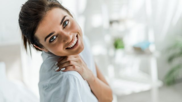 beautiful smiling girl looking at camera in bedroom in the morning
