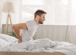 Side view of a frowned young man suffering from pain in loin while sitting on white bedding