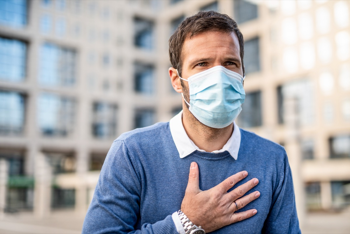 Man having a chest pain and wearing a protection mask.