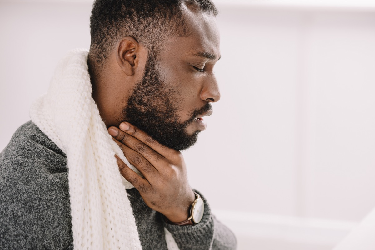 Sick man having sore throat.