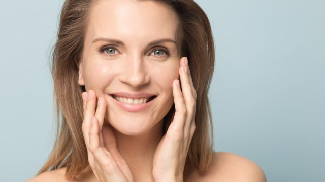 smiling woman touching perfect smooth face skin, looking at camera