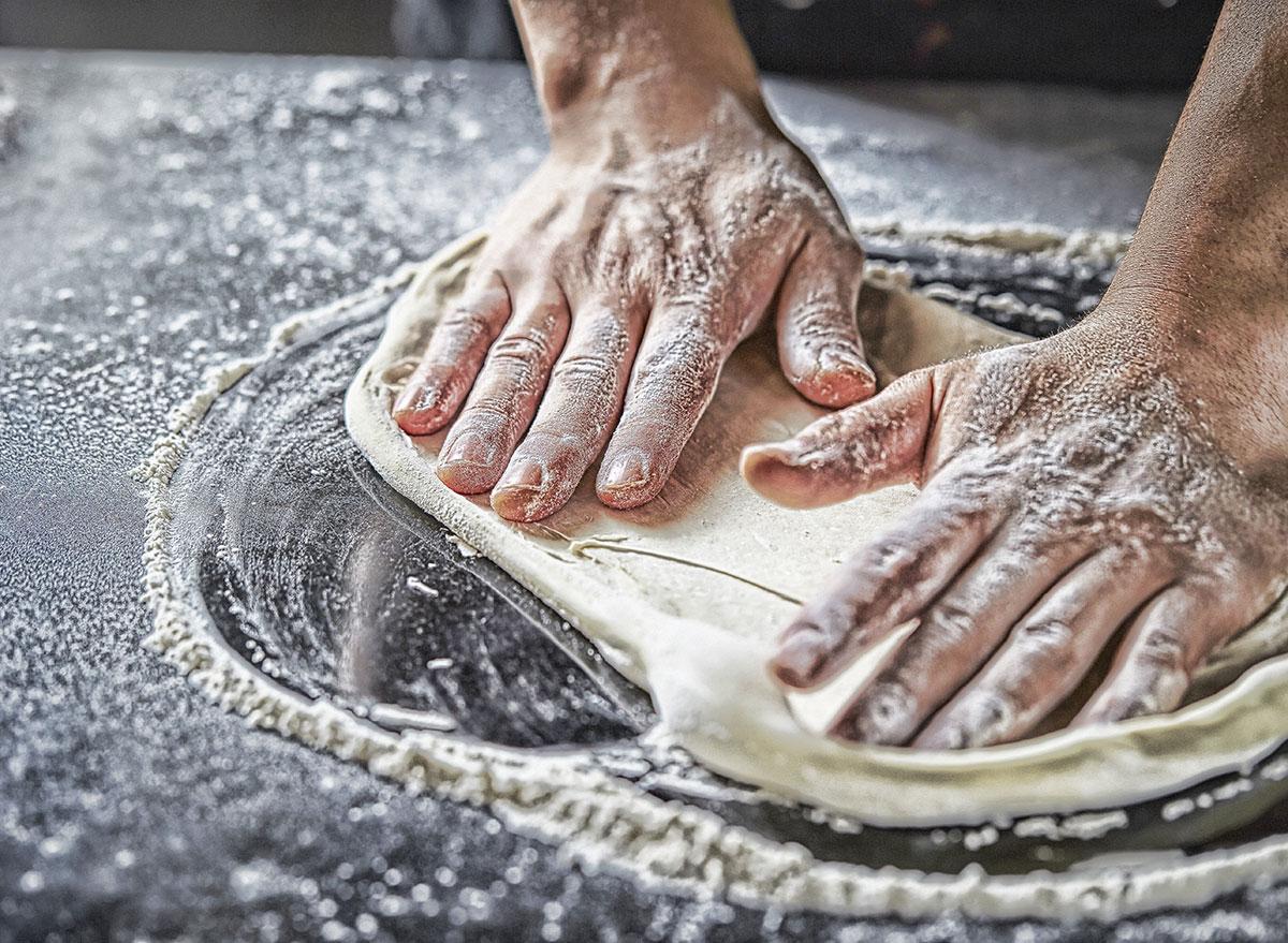 spreading pizza dough