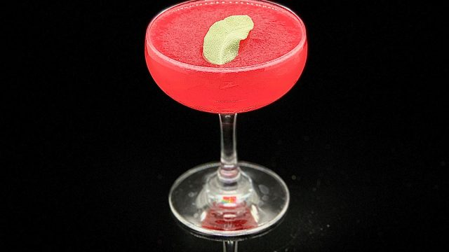 A pink and green nightcap cocktail drink on a black background