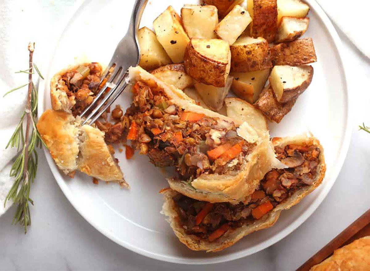 vegan beef wellington with roasted potatoes on plate