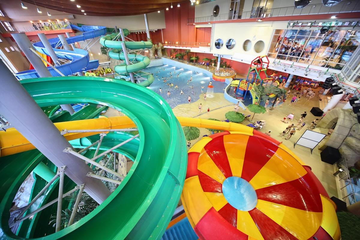 Large varicoloured chutes as spiral and pool in water park.