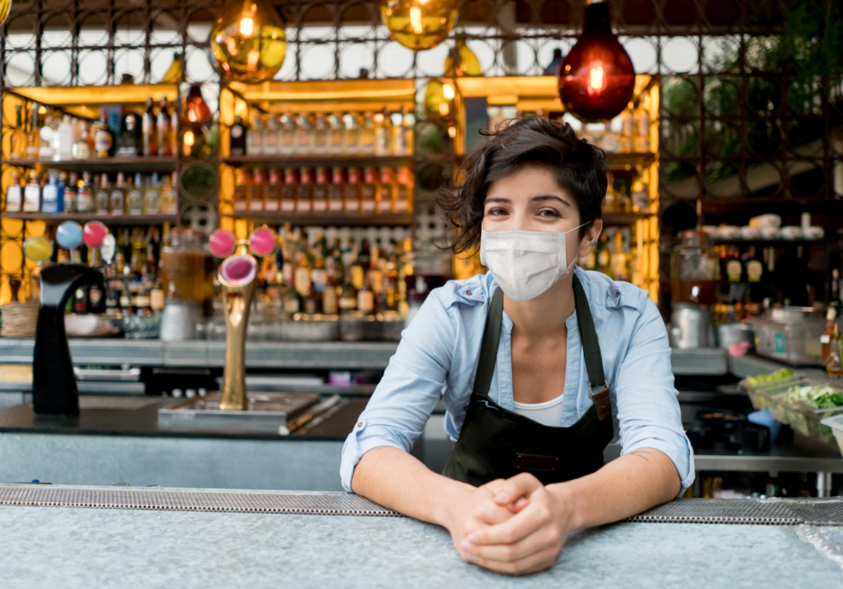 Portrait of a happy waitress working at a restaurant wearing a facemask.