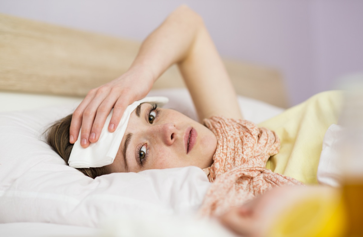 Sick woman lying in bed with high fever.