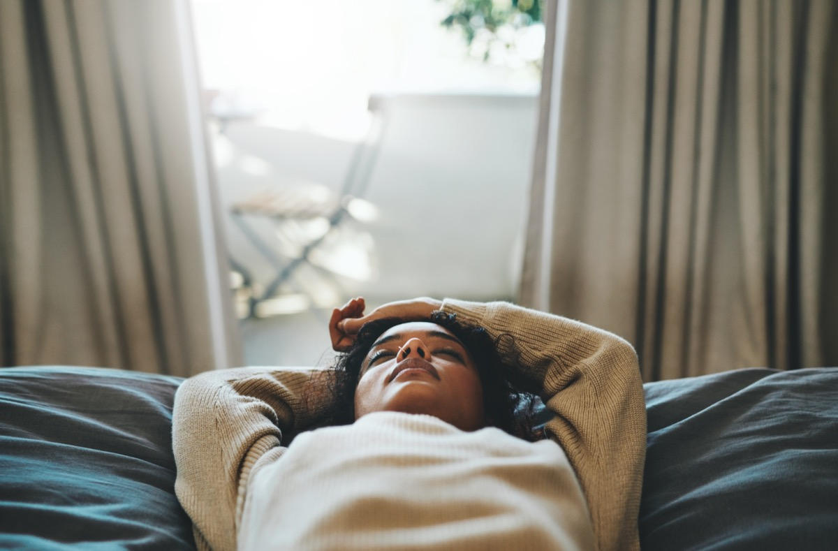 Woman lying on her bed with her eyes closed.