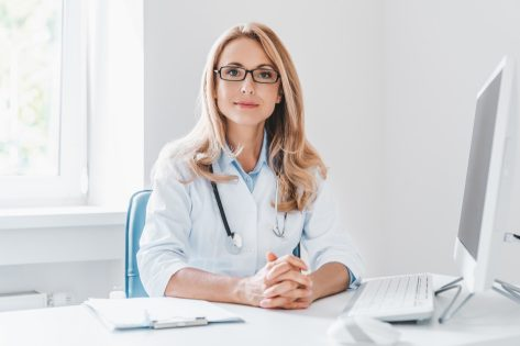 Portrait of adult female doctor sitting at desk in office clinic