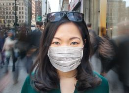 Woman in crowd wearing surgical mask.