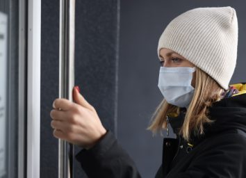 Young woman in protective medical mask and warm clothing opening door to store