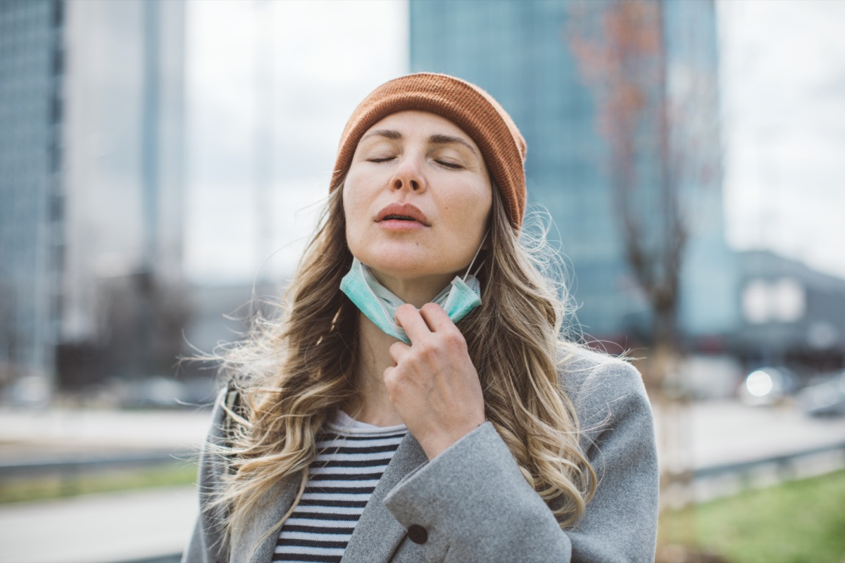 Woman removing face mask from her face outdoors.