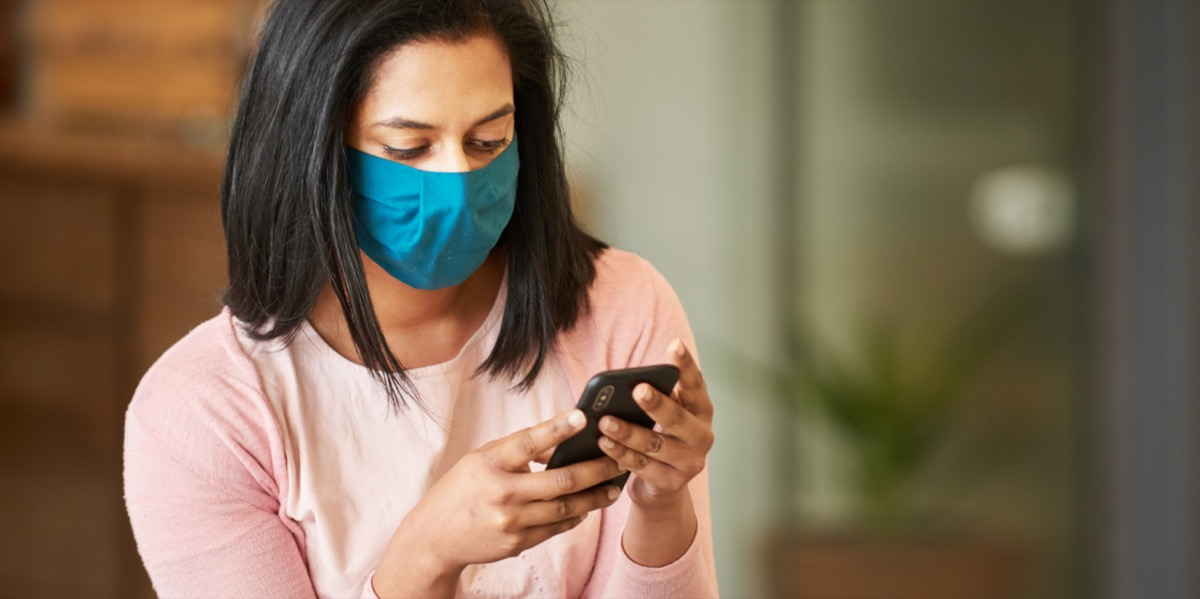 Woman with face protective mask looking at phone.