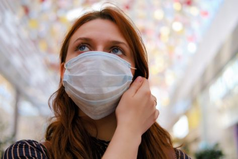 A young woman is considering whether to remove the medical mask after the end of the quarantine due to the coronavirus.