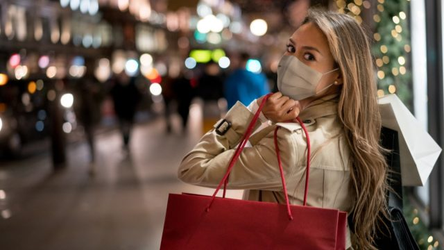 Happy woman Christmas shopping wearing a facemask