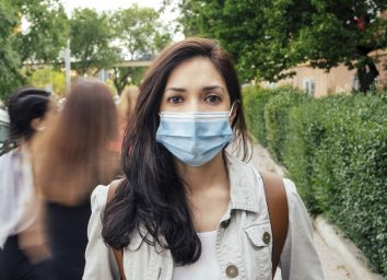 Woman covering her face with protective mask.