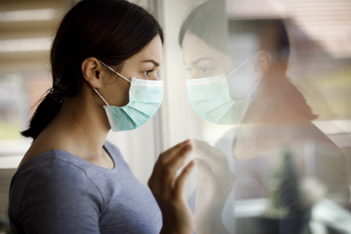 Sad woman with face protective mask looking through the window at home.