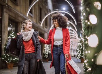Women Friends Smiling Broadly In Cheerful Manner Having Fun At Shopping Mall, Buying Christmas Gifts