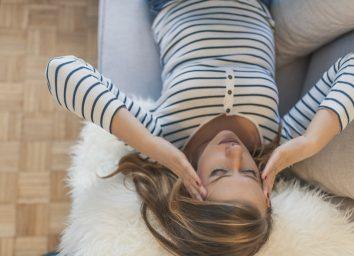 A woman on sofa, holding her head, having a strong headache.