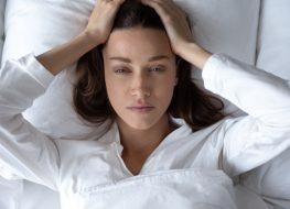 Disturbed woman lying awake in bed suffer from insomnia headache