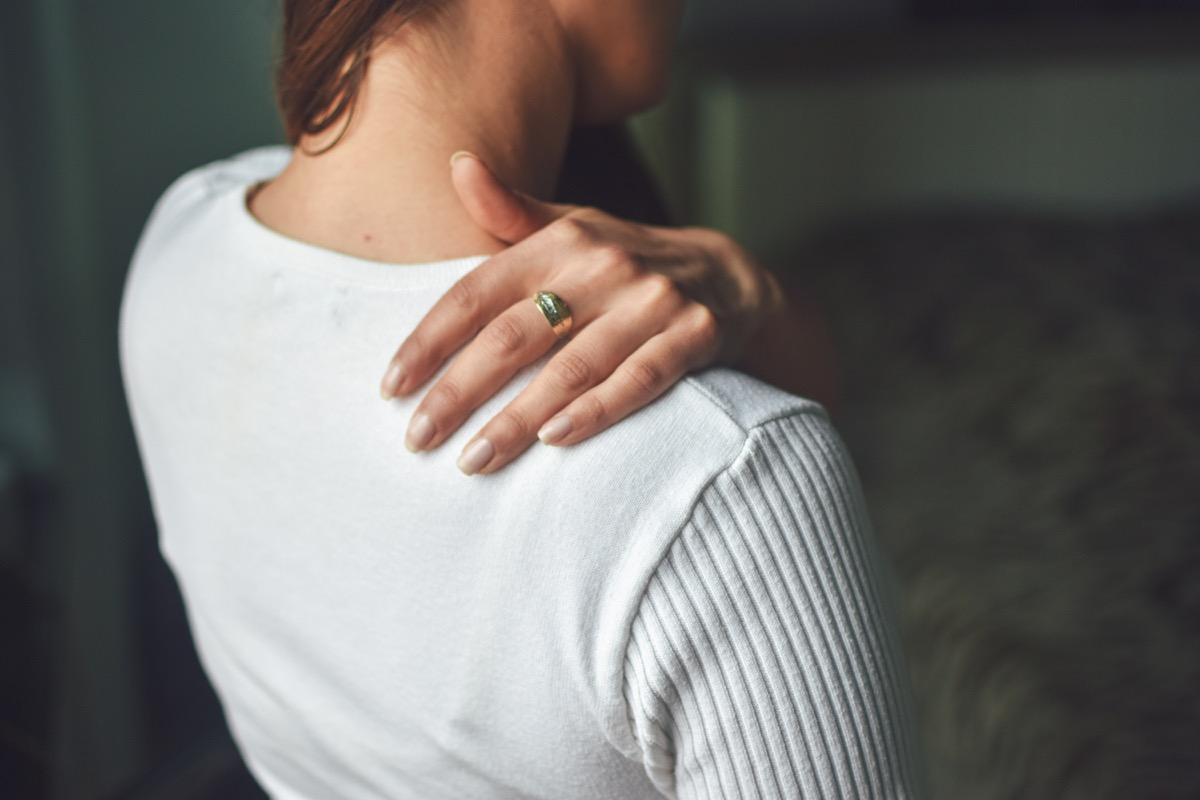 Woman is touching her stiff shoulder.