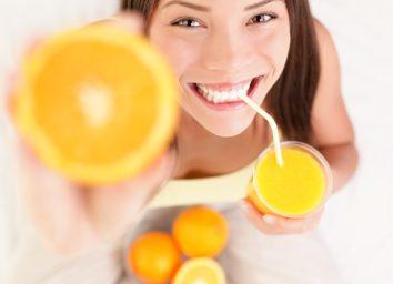 Woman drinking orange juice smiling showing oranges.